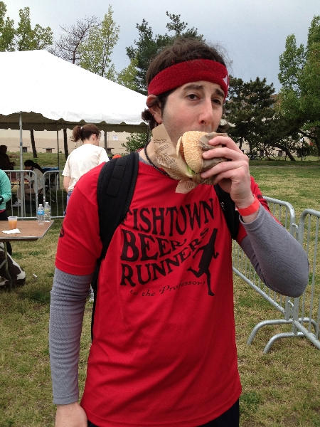 Lee eats a shad cake sandwich at Shad Fest (Philly)