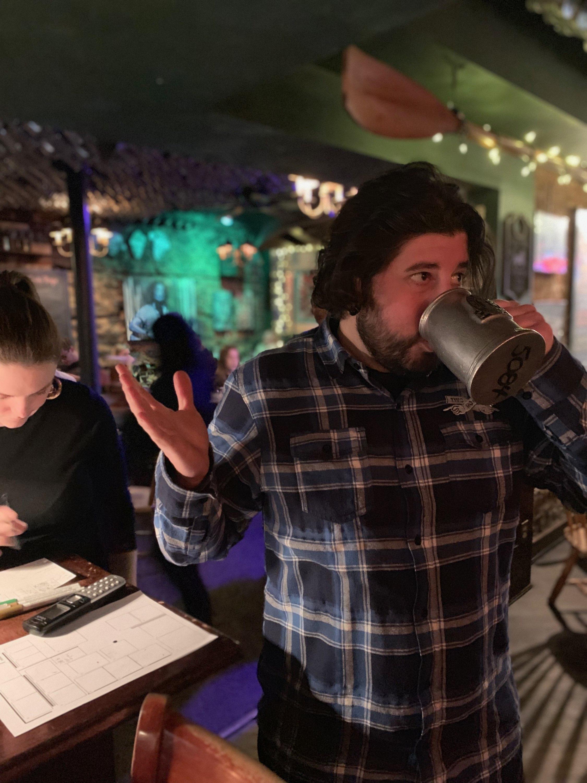 Lee shrugs and drinks w his mug at Porters' Pub (Pre-Covid).
