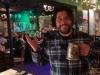Lee shrugs w his mug at Porters' Pub (Pre-Covid).